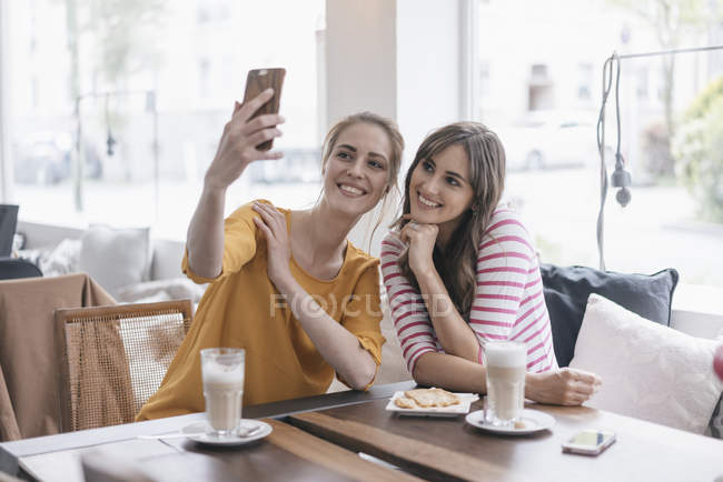 Zwei Freundinnen machen Selfie im Café — Stockfoto