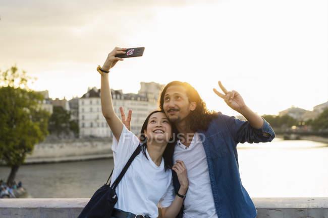 Франція, Париж, щаслива молода пара беручи селфі на річці Сени на заході сонця — стокове фото
