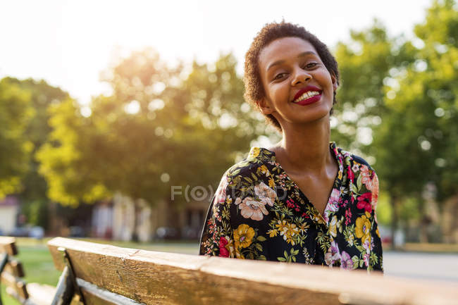 Портрет усміхнена молода жінка на лавці в парку — стокове фото