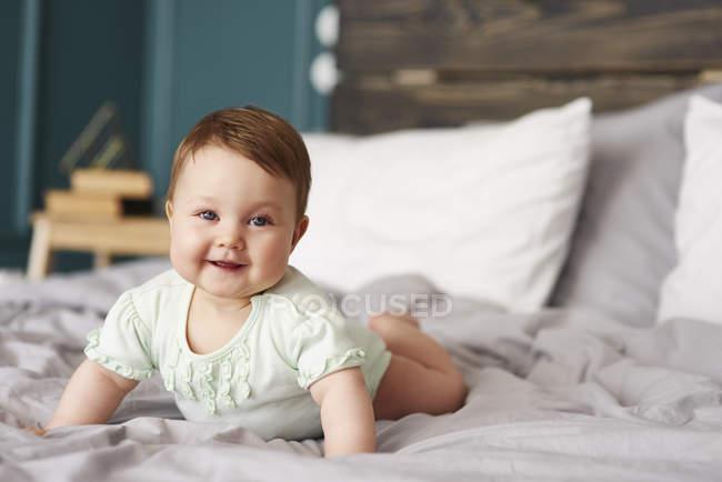 Retrato do bebê feliz que encontra-se na cama em casa — Fotografia de Stock