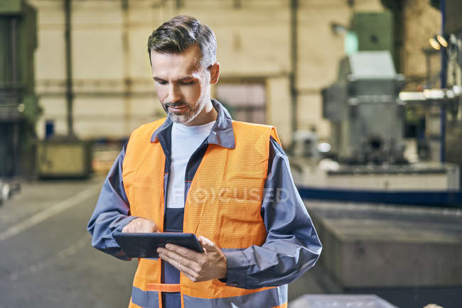 Man in protective workwear using tablet in factory — Stock Photo