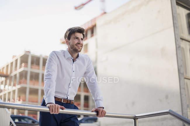 Porträt eines lächelnden Geschäftsmannes in der Stadt, der sich an Geländer lehnt — Stockfoto