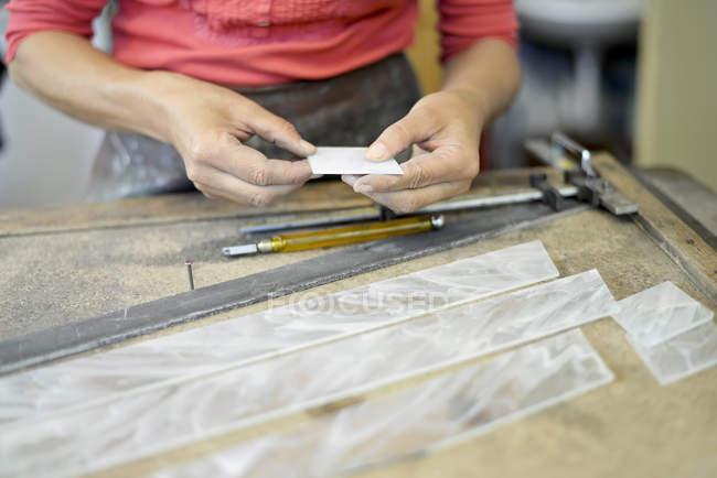 Крупний план жінки, яка працює над шматком скла в майстерні гламп'є — стокове фото