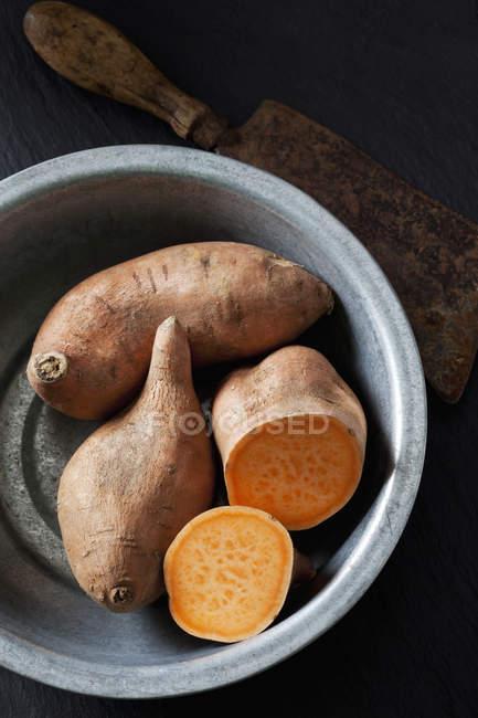 Нарезанный и весь сладкий картофель в металлической миске — стоковое фото