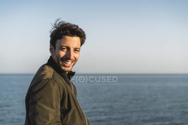 Retrato de um jovem sorridente na praia — Fotografia de Stock