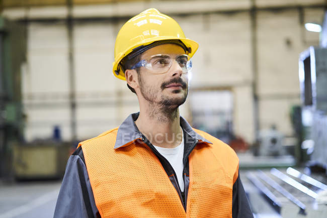 Man wearing protective workwear looking around in factory — Stock Photo