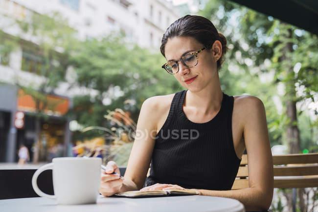 Jeune femme assise dans un café, remue-méninges, notes d'écriture dans un carnet — Photo de stock