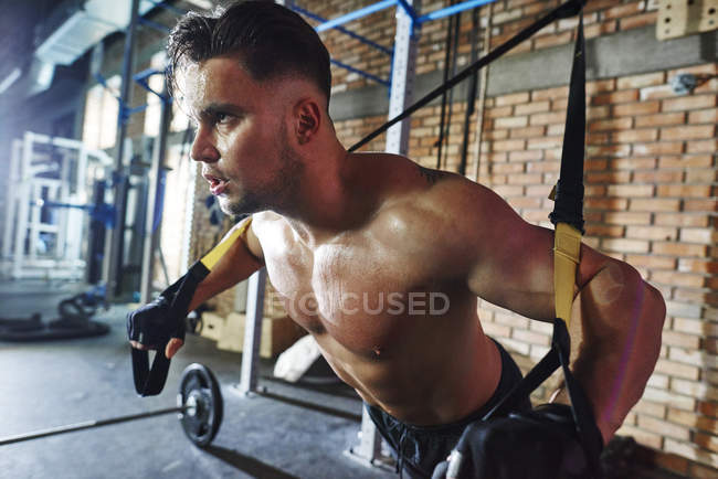Man doing exercise with suspension straps in gym — Stock Photo