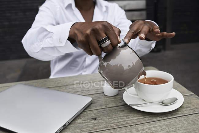 Обрезанный образ деловой женщины, сидящей на террасе кафе и наливающей чай в чашку — стоковое фото