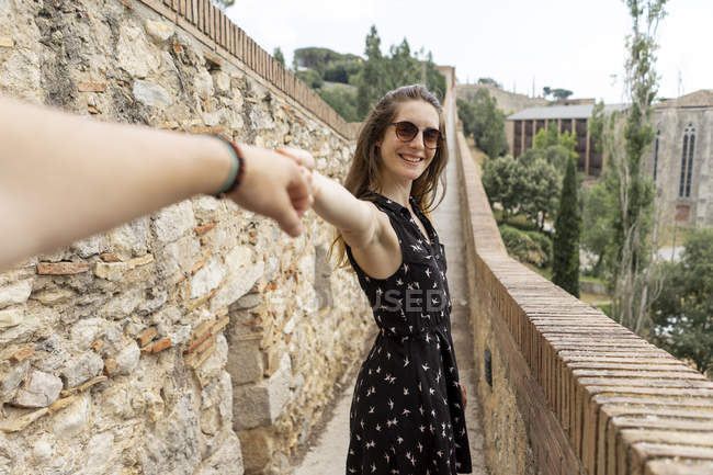 Spain, Girona, smiling woman holding man's hand walking along stone wall — стокове фото
