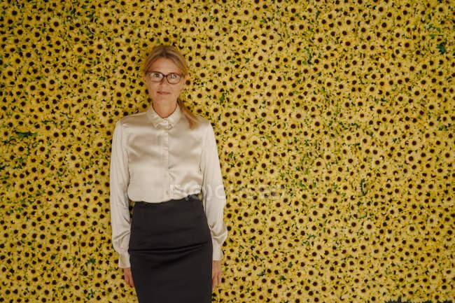 Porträt einer Geschäftsfrau, die mit Sonnenblumen an der Wand steht — Stockfoto