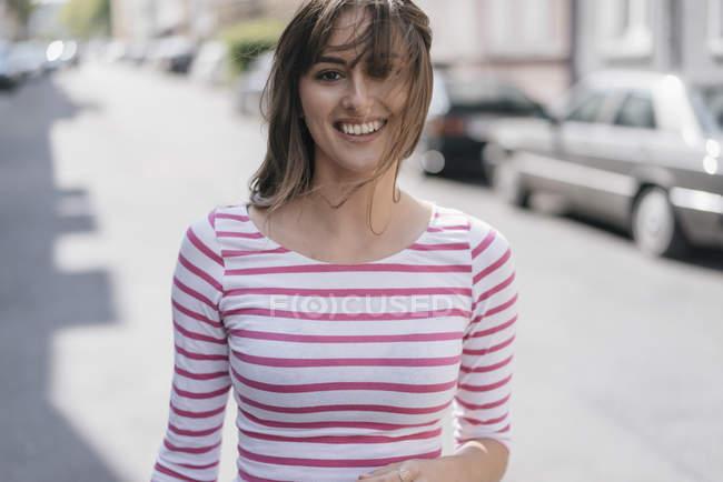 Joyeux jeune femme marchant en ville — Photo de stock