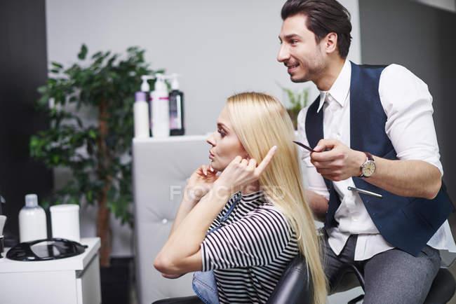 Femme parlant au coiffeur dans le salon de coiffure — Photo de stock