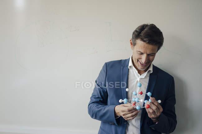 Homme d'affaires prospère appuyé sur le tableau blanc, tenant le modèle de molécule — Photo de stock