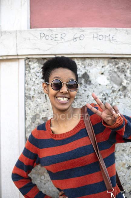 Портрет усміхнена молода жінка, що носить сонцезахисні окуляри і смугастий пуловер показуючи знак перемоги — стокове фото