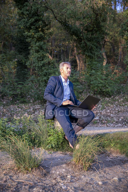 Mature businessman with laptop sitting barefoot in nature and looking at distance — Fotografia de Stock