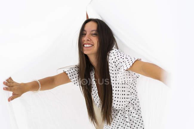 Porträt einer jungen Frau, die Spaß beim Trocknen von Bettlaken auf der Dachterrasse hat — Stockfoto