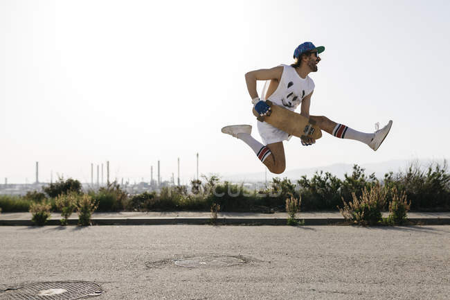 Sportive man jumping above ground with skateboard in hands — Stock Photo