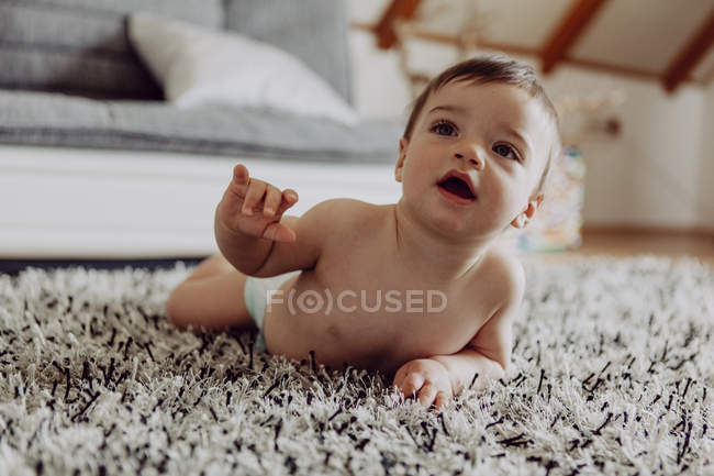 Happy baby boy playing on carpet — Stock Photo