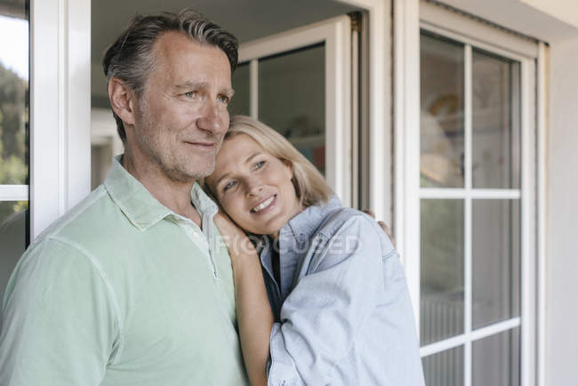 Retrato de pareja madura sonriente en la ventana francesa - foto de stock