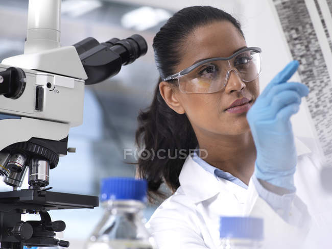 Genetic Research, female scientist holding a foil with genetic code, the genetic make-up — Stock Photo