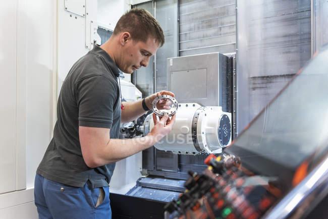 Un homme examine une pièce à la machine dans une usine — Photo de stock