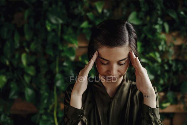 Орієнтована молода жінка на стіні з альпіністські рослинами — стокове фото