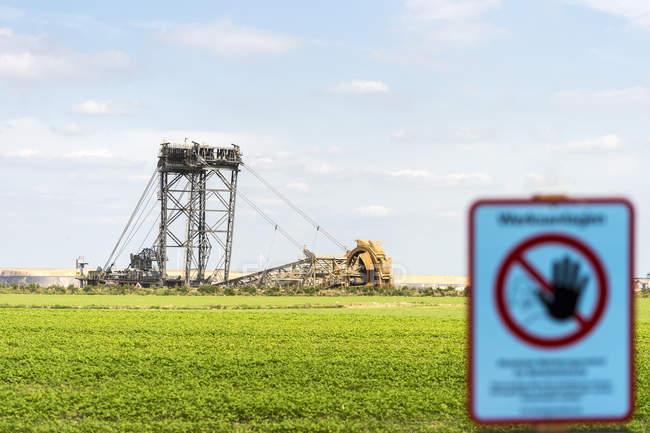 Alemania, mina de superficie Garzweiler, señal de advertencia y excavadora de cubo gigante - foto de stock