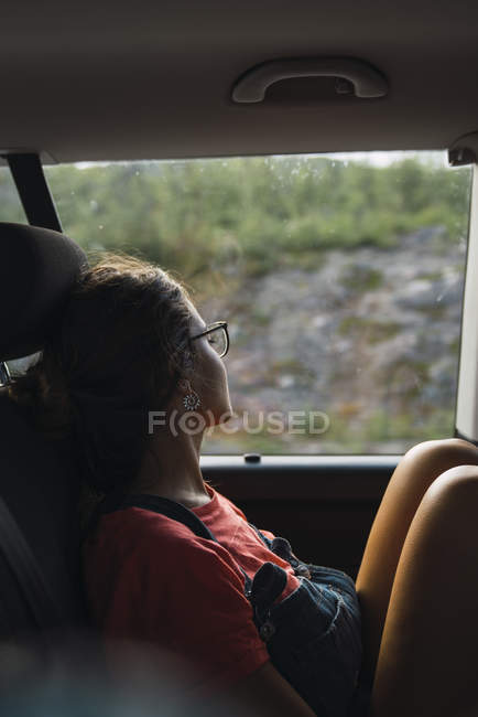 Young woman sitting on back seat of a van, looking out of window, traveling concept — Stock Photo