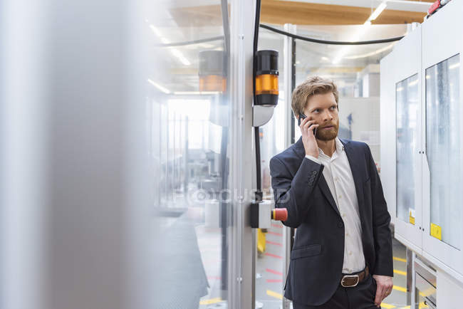Businessman on cell phone at machine in modern factory — Stock Photo