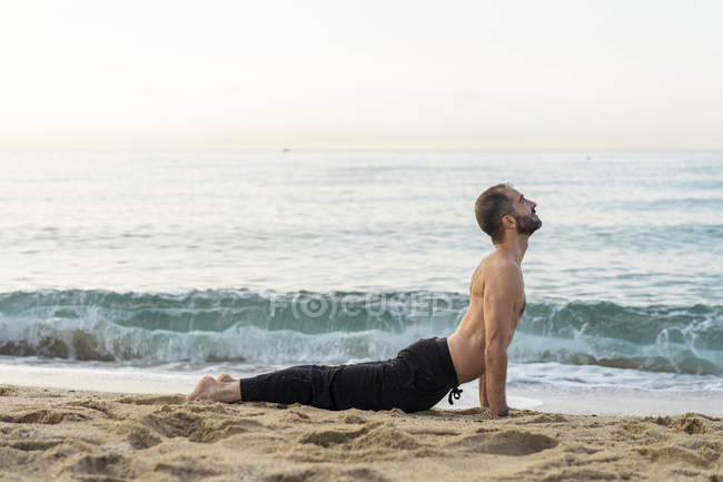 Spain. Man doing yoga on the beach in the evening, cobra pose — стоковое фото