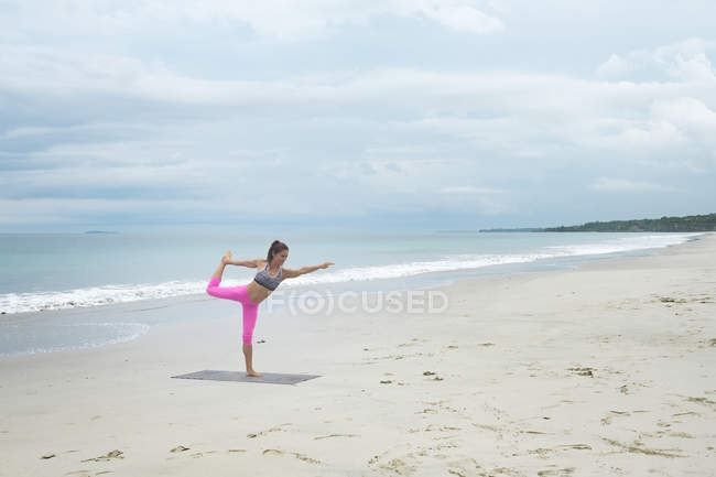 Woman practicing yoga balancing on beach — Stock Photo