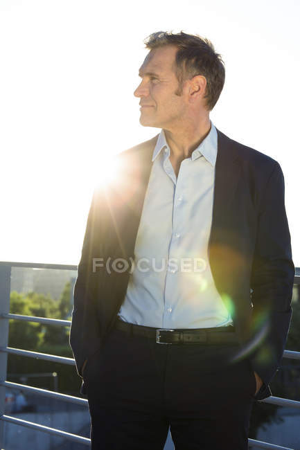 Confident mature businessman on a bridge in backlight — Stock Photo