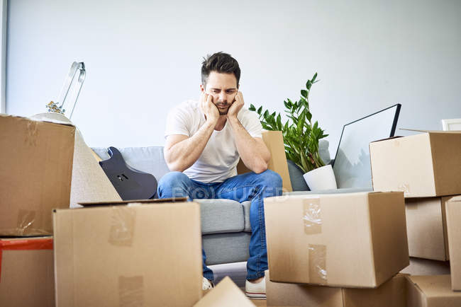 Frustrated man sitting on couch surrounded by cardboard boxes — Stock Photo