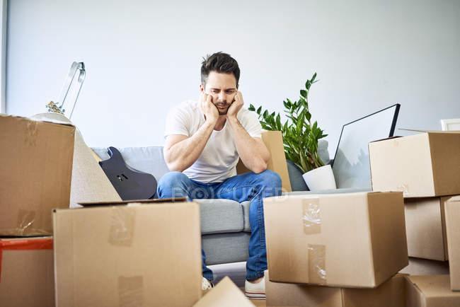 Uomo frustrato seduto sul divano circondato da scatole di cartone — Foto stock
