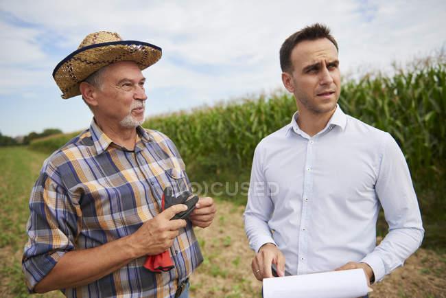 Bauer mit Hut und Geschäftsmann diskutieren über Feld — Stockfoto