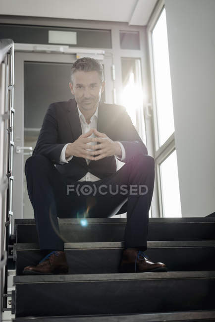 Portrait of confident businessman sitting on stairs — Stock Photo
