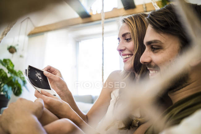 Happy couple looking at ultrasound scans — Stock Photo
