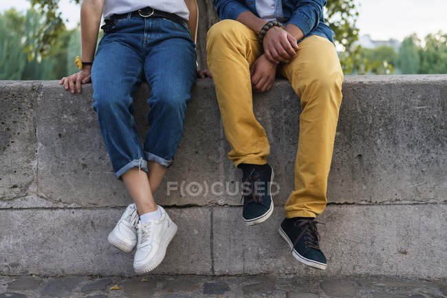 Legs of a couple sitting on a wall — Stock Photo