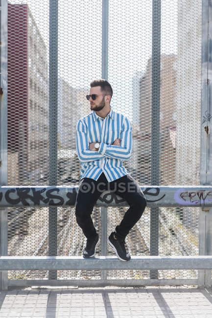 Молодой человек сидит на заборе — стоковое фото