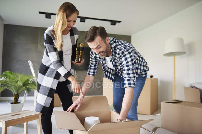Happy couple moving into new flat unpacking cardboard box — Stock Photo