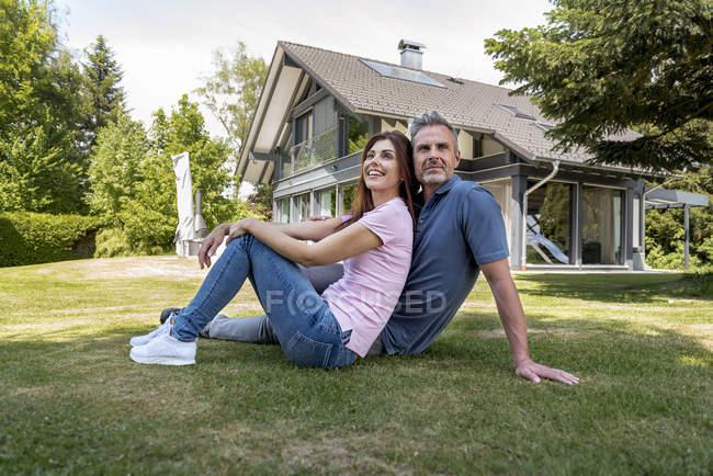 Casal feliz sentado no jardim de sua casa — Fotografia de Stock