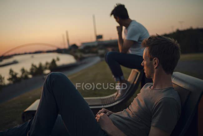 Два друга смотрят закат на реке — стоковое фото