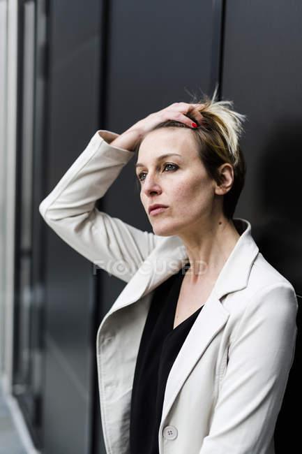 Porträt einer nachdenklichen Geschäftsfrau an schwarze Wand gelehnt — Stockfoto