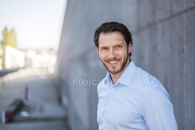 Retrato de homem de negócios sorridente na parede de concreto — Fotografia de Stock