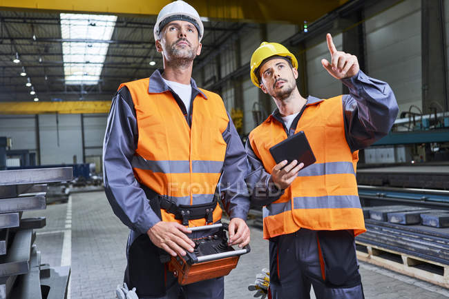 Men in factory talking and operating machinery with remote console — Stock Photo