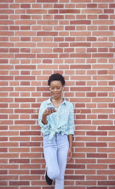 Lächelnde Frau lehnt mit Kopfhörern und Handy an Ziegelwand — Stockfoto