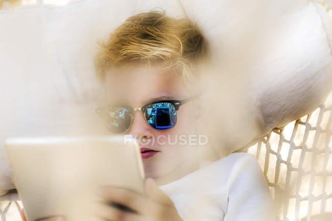 Boy wearing sunglasses lying in hammock using tablet — Stock Photo