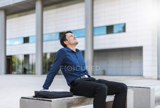 Бизнесмен, сидящий на улице, откидываясь назад — стоковое фото
