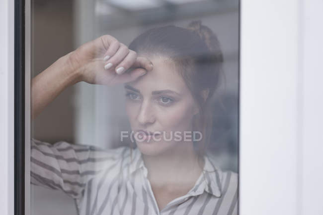 Close-up of lonely woman looking out of window — Stock Photo